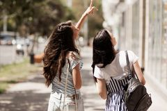 Two friendly cute girls with long dark hair,wearing casual outfit,walk down the street and hold hands. royalty free stock photo
