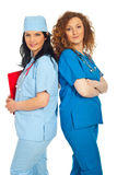 Two friendly doctors women. Standing back to back isolated on white background royalty free stock photography