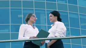 Two friendly female coworkers doing business outdoors. One of them presents her work to another stock video footage
