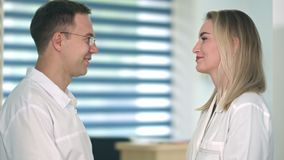 Two friendly female and male doctors talking in the hospital. Close up shot. Professional shot in 4K resolution. 098. You can use it e.g. in your commercial stock footage