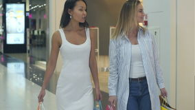 Two friendly females chatting while walking in the mall. Professional shot in 4K resolution. 103. You can use it e.g. in your commercial video, business stock footage