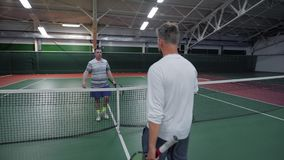 Two friendly male tennis players after the game. They going to each other stock footage