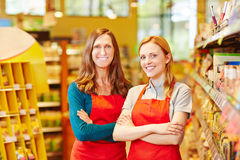 Two friendly saleswomen in a supermarket Royalty Free Stock Photos