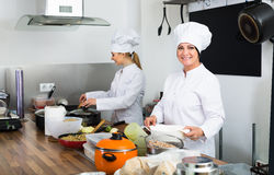 Two friendly women chefs cooking food at kitchen. Two friendly women chefs cooking food at cafe's kitchen royalty free stock image