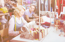 Two friendly women tailors working with sewing machines. At studio stock photography