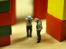 Two friends. Two litle old man figures chatting (selective focus on first figure stock photo