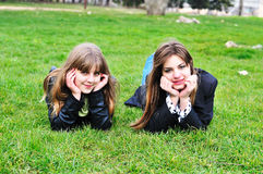 Two friends. Two cheerful teen girls laying on the green grass Royalty Free Stock Image