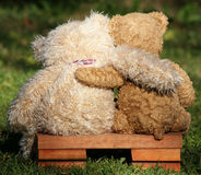 Two friends. Two teddy bears on a bench with arms around each other Royalty Free Stock Image