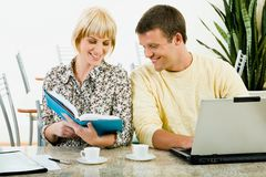 Two friends. Beautiful woman is holding a book and demonstrating a text to her boy friend in the cafe Royalty Free Stock Photos