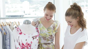 Two friends admiring a dress on a mannequin. In a boutique stock video footage