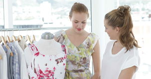 Two friends admiring a dress on a mannequin. In a boutique stock video