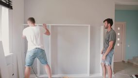 Two friends assembling the shelf, do the repairs. Man helping to his friend moving to new house. Two friends assembling the bookshelf, do the repairs together stock video