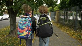 Two Friends with Backpacks are Going to School on City Streets past Cars. Sister with her Brother Back to School. Sun is stock video footage