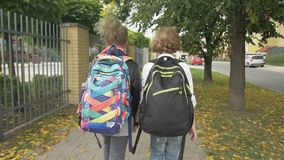 Two Friends with Backpacks are Going to School on City Streets past Cars. Sister with her Brother Back to School. Sun is stock footage