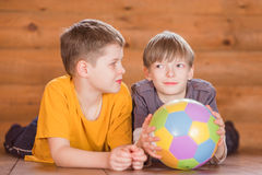 Two friends with a ball lying on the floor Royalty Free Stock Images