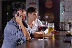 Two friends at the bar with a woman on a mobile Royalty Free Stock Photos