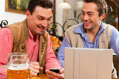 Two friends in Bavarian pub with laptop Royalty Free Stock Images