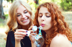 Two friends blowing soap bubbles Stock Photos