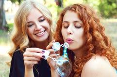 Two friends blowing soap bubbles Stock Photos