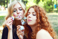 Two friends blowing soap bubbles Stock Image