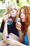 Two friends blowing soap bubbles Royalty Free Stock Photos