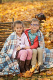 Two friends: a boy and a girl in autumn park sitting on wooden bench near a fence Royalty Free Stock Photography