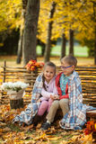 Two friends: a boy and a girl in autumn park sitting on wooden bench near a fence Stock Images