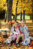 Two friends: a boy and a girl in autumn park sitting on wooden bench near a fence Stock Photography