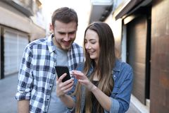Two friends browsing phone content walking in the street stock photography