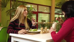 Two women are sitting in a fitness club cafe eating salad and drinking a protein cocktail, slow motion. Two friends in the cafe fitness club stock footage