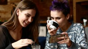 Two friends in a cafe watch video on the smartphone and laugh. Women drink coffee in the coffee house.  stock footage