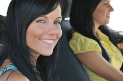 Two friends in car. Two smiling friends (teenage girls) driving in car - focus on front woman Stock Images