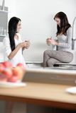 Two friends catching up in the kitchen Royalty Free Stock Images