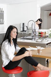 Two friends catching up in the kitchen. Two friends catching up over coffee in their kitchen Royalty Free Stock Photos
