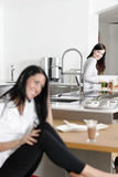 Two friends catching up in the kitchen. Two friends catching up over coffee in their kitchen Royalty Free Stock Images