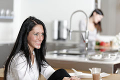 Two friends catching up in the kitchen. Two friends catching up over coffee in their kitchen Royalty Free Stock Photo