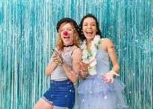 Two friends are celebrating Carnaval. Blue color predominant. Co. Two friends have fun at Carnaval. One is wearing clown nose and the other Hawaiian necklace Royalty Free Stock Image