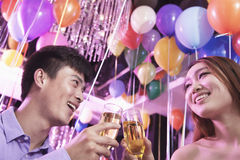Two friends celebrating, toasting with champagne, nightclub in Beijing, balloons in the background Stock Photo
