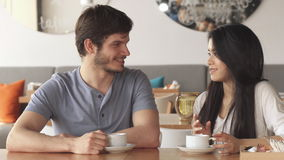 Two friends chat at the cafe. Two young friends of different genders chatting at the cafe. Handsome caucasian guy and pretty asian girl looking at each other stock video footage