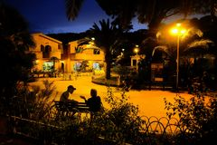 Chatting in the blue hour. Two friends chatting on a bench at night in a small Sardinian town stock photography