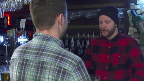 Two friends chatting at the pub. Two caucasian friends chatting at the pub. Attractive bearded guy in red checkered shirt and black hat gesturing by his hands stock video footage