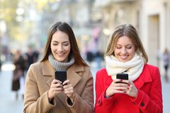 Two friends checking smart phones in the street stock image