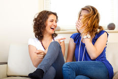 Two friends on a couch laughing and having fun. Shot in location with studio lights Stock Photography