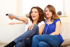 Two friends on a couch watching tv. Shot in location with studio lights Royalty Free Stock Photography