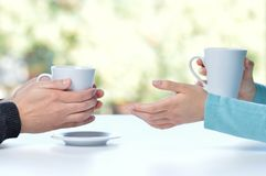 Two friends or couple talking holding coffee cups sitting in a table at home with a window in the stock photos