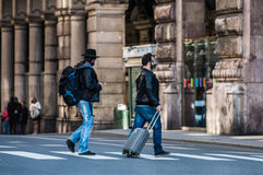 Two friends are crossing the street in busy area. Royalty Free Stock Images