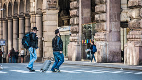 Two friends are crossing the street in busy area. Two guys are walking through the streets of Genova, Italy and looking around, talking to each other. Touristic Stock Photo