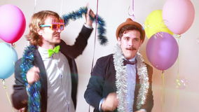 Two friends dancing and giving double high five in photo booth. Two male friends dancing and giving double high five in party photo booth, graded stock footage