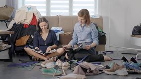 Two friends decided to arrange a wardrobe. Women were tired and sat on the floor to relax and read a magazine. Houses have fun together stock video footage
