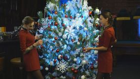Two friends decorating a Christmas tree stock video footage